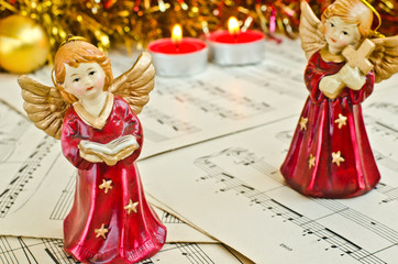Christmas figurine of angels on a music sheet.