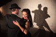 Two tango dancers performing under spotlight indoors