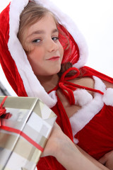 Little girl in a Santa outfit with Christmas presents