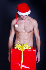 Portrait of a handsome muscular young man in Santa Claus hat