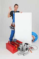 Female plumber with tools of the trade and a board