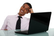 Happy businessman sat at his desk