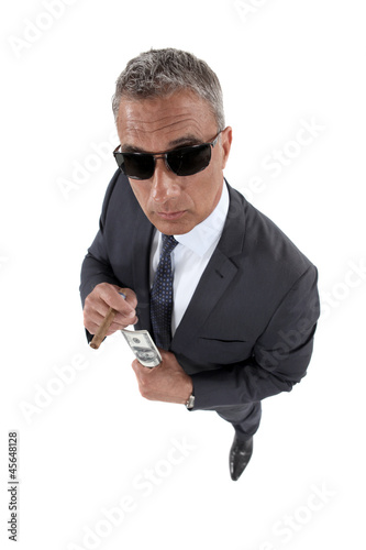 businessman holding money and smoking a cigar