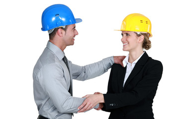 Male and female architects shake hands