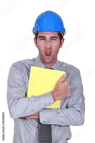 Man yawning whilst clutching paperwork