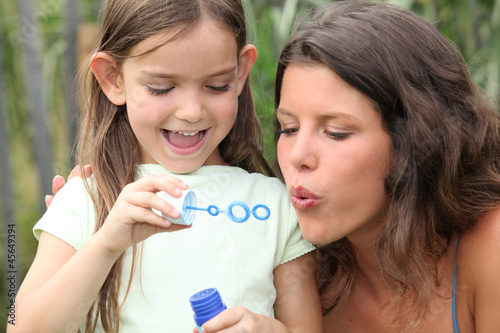 Mom and girl making soap bubbles