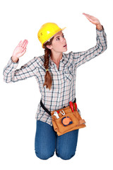 Tradeswoman patting invisible walls