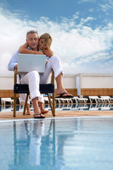 Couple looking at a laptop by a pool