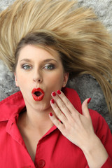 Shocked blond woman laying on rug