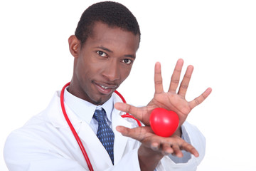 Male doctor holding heart shaped toy