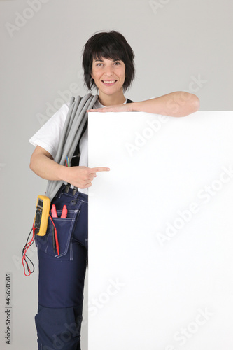 Female electrician posing with blank message board