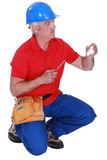 Tradesman holding a plug and a screwdriver poster