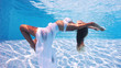 Underwater woman fashion portrait in swimming pool.