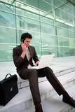 Businessman sat on steps working