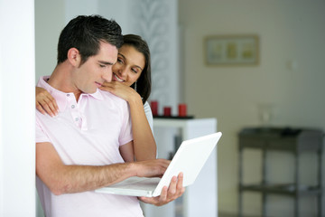 Couple stood at home with a laptop computer