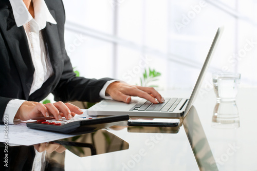 Female office worker doing accounting with calculator.