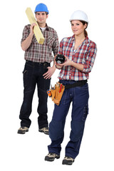 Two carpenters stood with piggy-bank