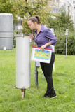 Young woman meteorologist inspecting meteorological instruments