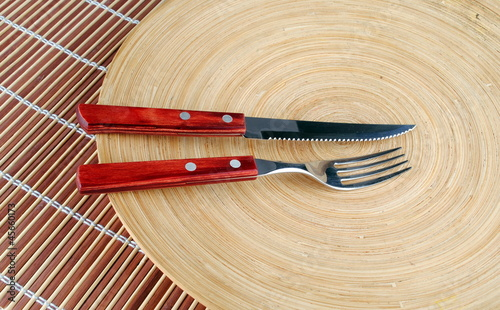 wooden round dish and red cutlery on bamboo