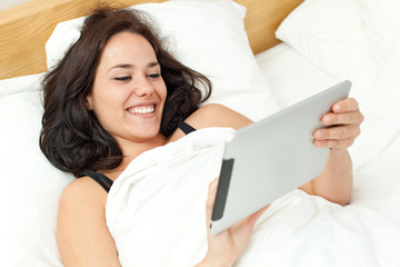 Woman in bed using an electronic tablet