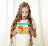 Little blond girl holding books and looking on it with amaze