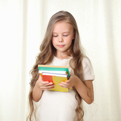 Little blond girl holding different books and looking on it