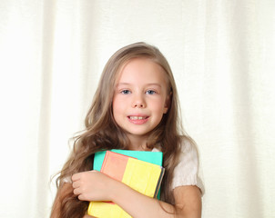 Little blond girl holding different books and smiling
