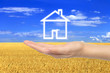 Virtual house with woman hand on wheat field background