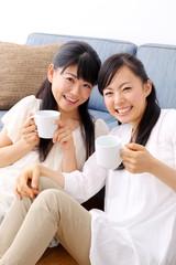 コーヒーカップを持つ女の子二人