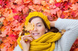 Frau im Herbst mit Bett aus Blättern rot und gelb