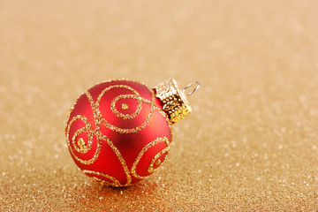 Red Christmas ball on golden background