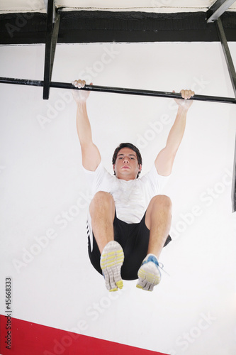 fit man performing pull ups in a bar