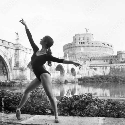 Young beautiful ballerina dancing in Tevere riverside in Rome