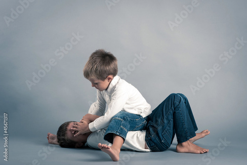 Two young brothers fighting.