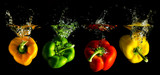Fototapety vier verschieden farbige Paprika fallen ins Wasser