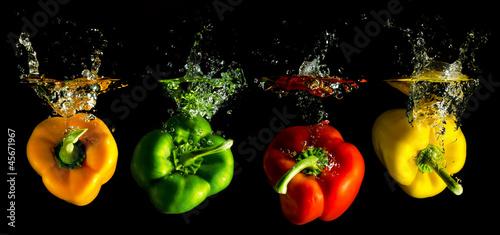 vier verschieden farbige Paprika fallen ins Wasser