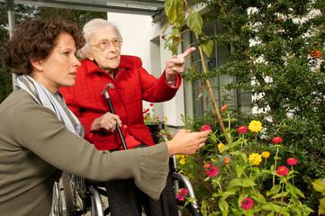 Seniorin im Rollstuhl mit junger Frau