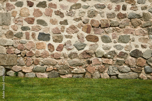 Background of stone wall and green grass
