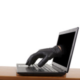 Internet theft - gloved hand reaching through a laptop.