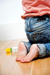 Kind mit nackten Füßen hockt
