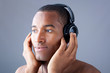 Young black man listening to music with headphones over grey bac