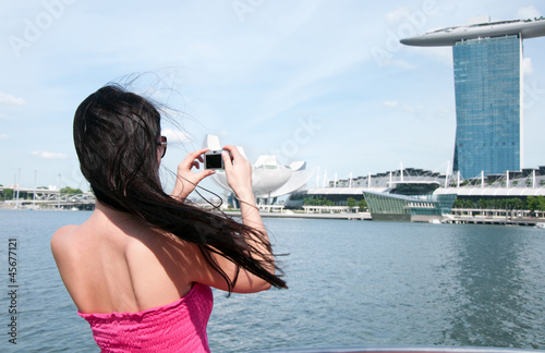 Young woman taking picture of Marina bay hotel in Singapore