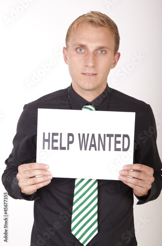 Young attractive man with a sign help wanted