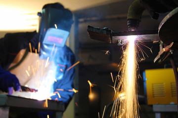 Steel workers welding and cutting in metal industry