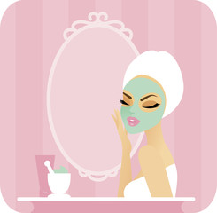 Young woman with a towel over her hair applying a facial mask