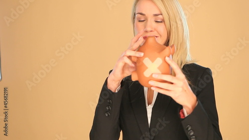 Blonde businesswoman with a piggybank