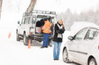 Mechanic helping woman with broken car snow