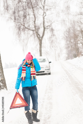 Woman with warning triangle car snow breakdown