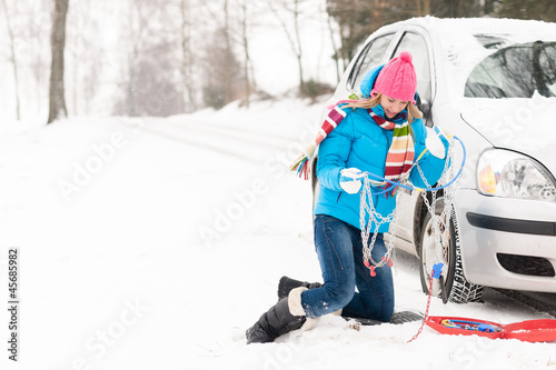 Woman with winter car tire chains snow