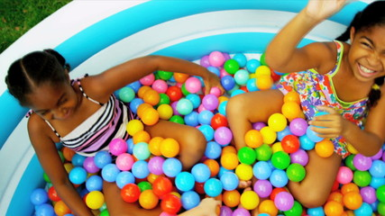 Ethnic Sisters Playing Ball Pool